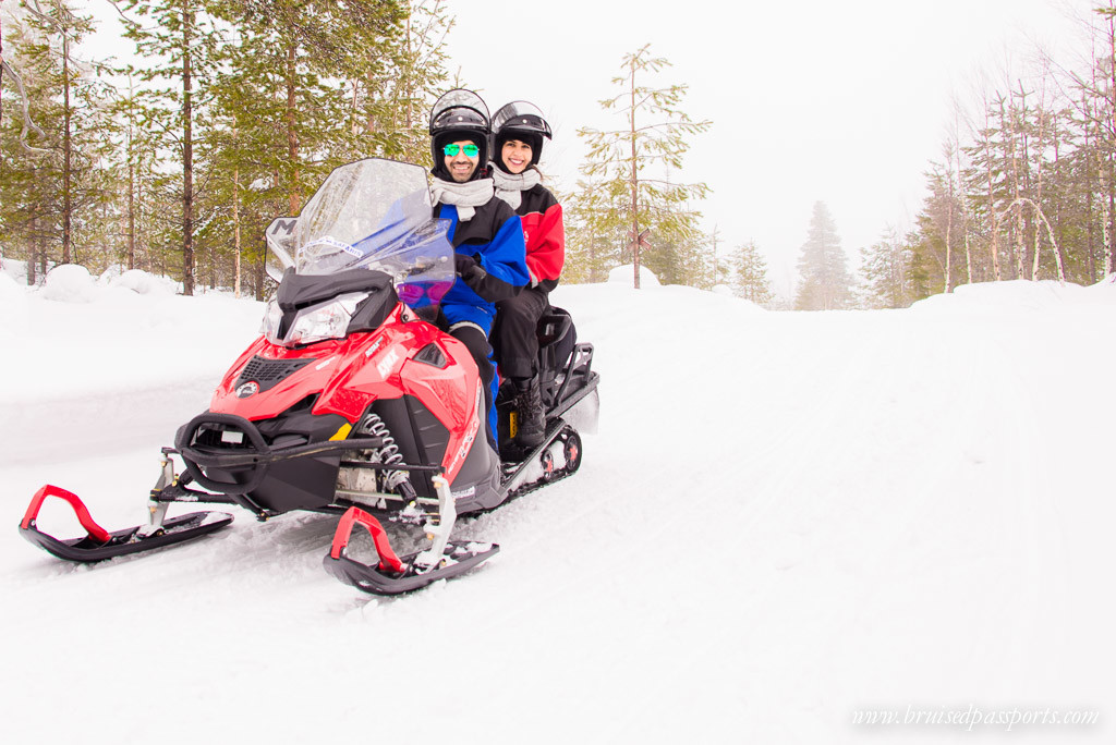 Us on our snowmobile driving into the Arctic forest in Rovaniemi