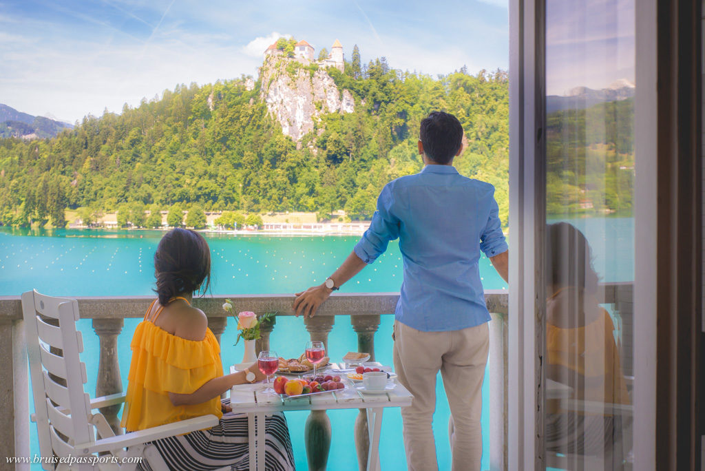 Couple enjoying breakfast on the balcony of Grand Hotel Toplice overlooking Bled Castle