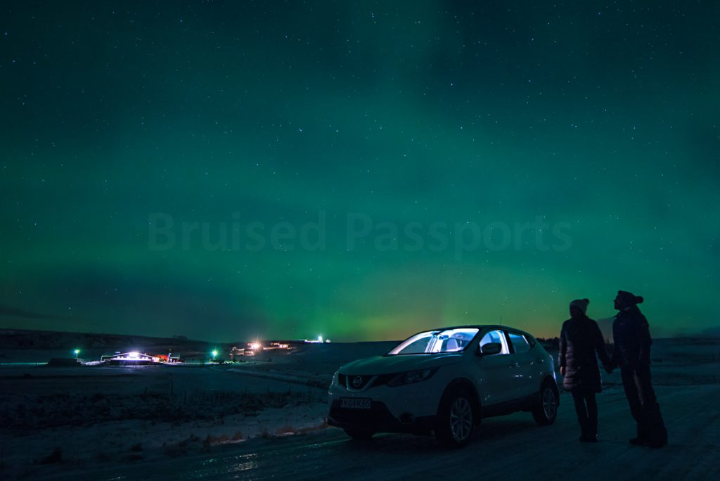 couple and their car under the Northern Lighst in Iceland