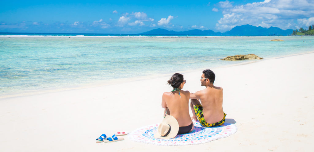 Couple sunbathing on beach at Silhouette Island