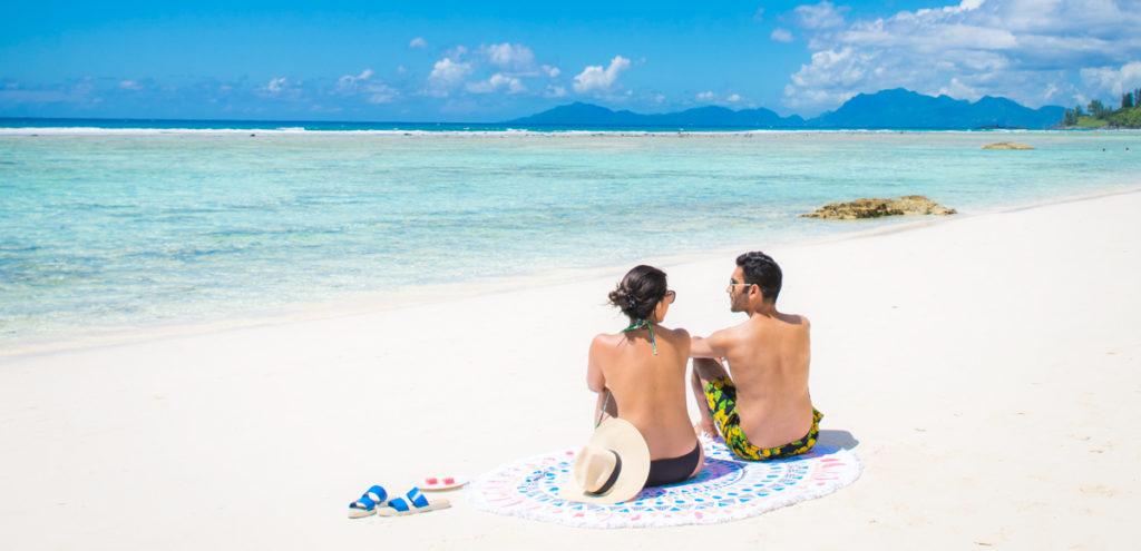 Couple sunbathing on beach at Silhouette Island