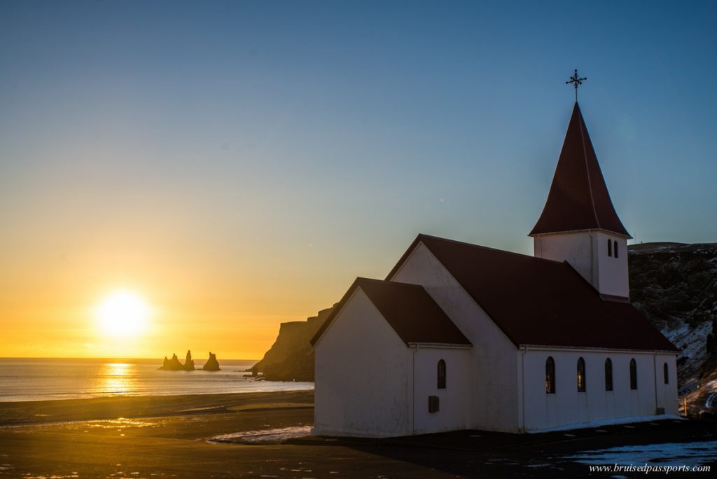 church of vik at sunset with the rocks at the back