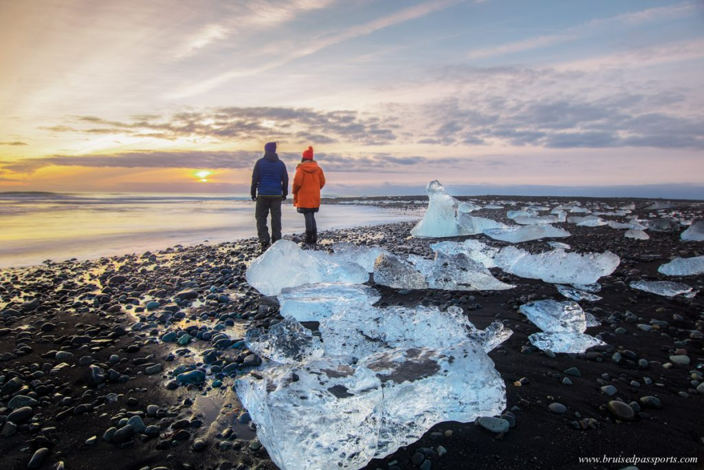 couple enjoying sunrise at Diamond beach near Jokulsarlon