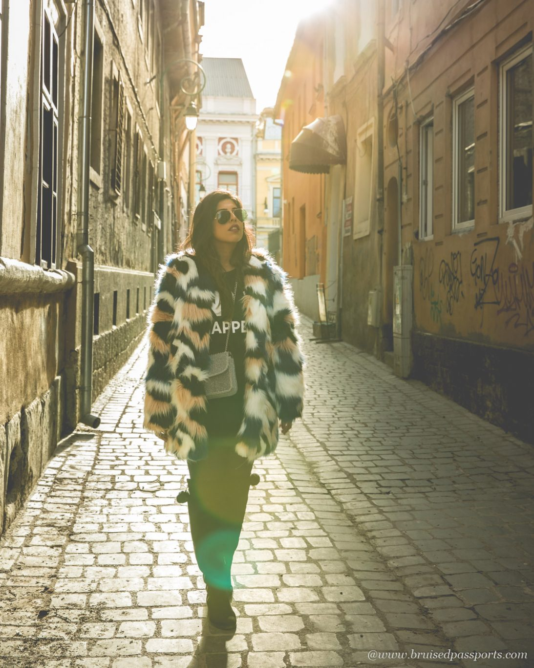 girl walking on cobbled streets in Brasov with fur jacket
