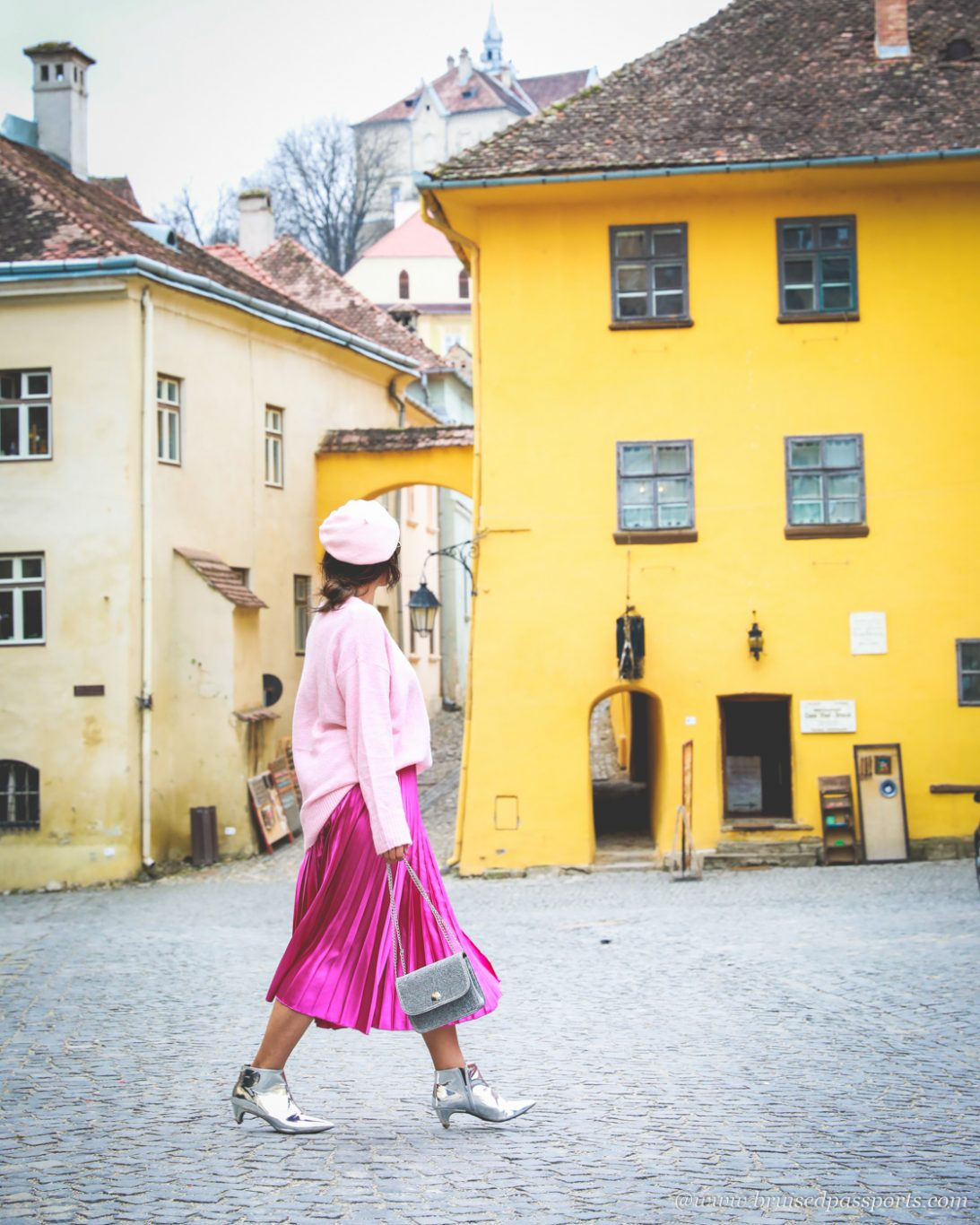 girl walking in front of coloured houses in Romania