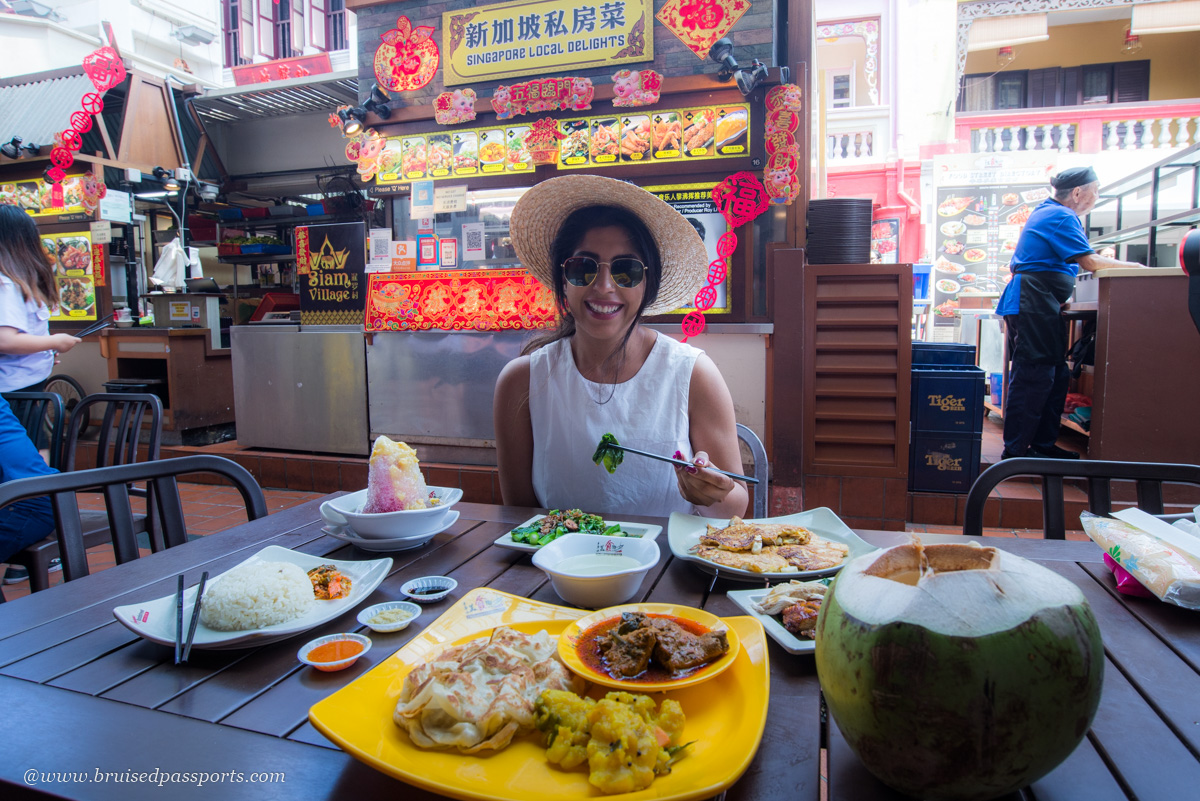 girl trying local cuisine at a hawker centre in Singapore