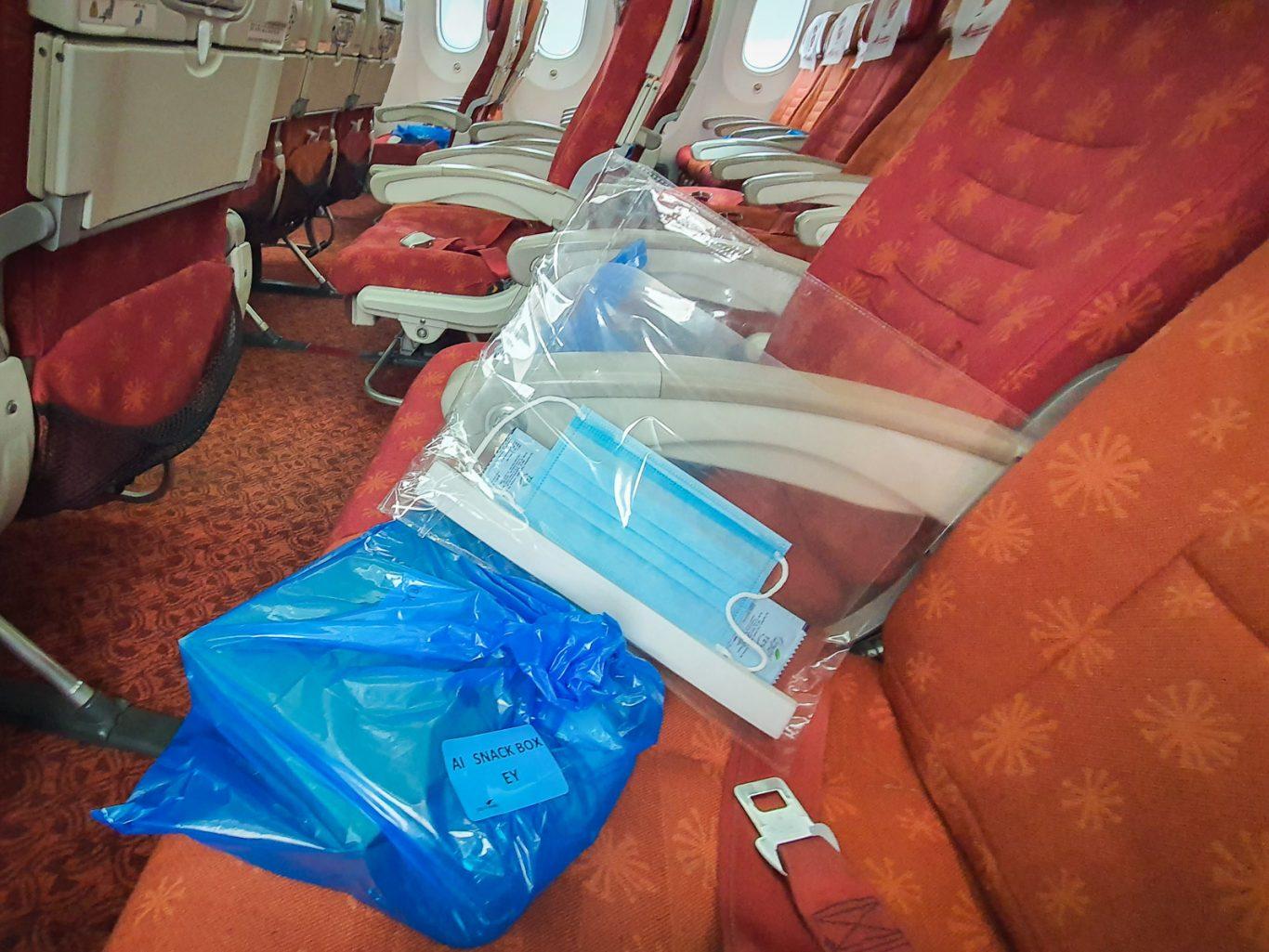Pre-packed snack boxes, masks, visor, and hand sanitiser on flight